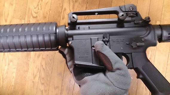 手袋で銃を揺らしながら取る