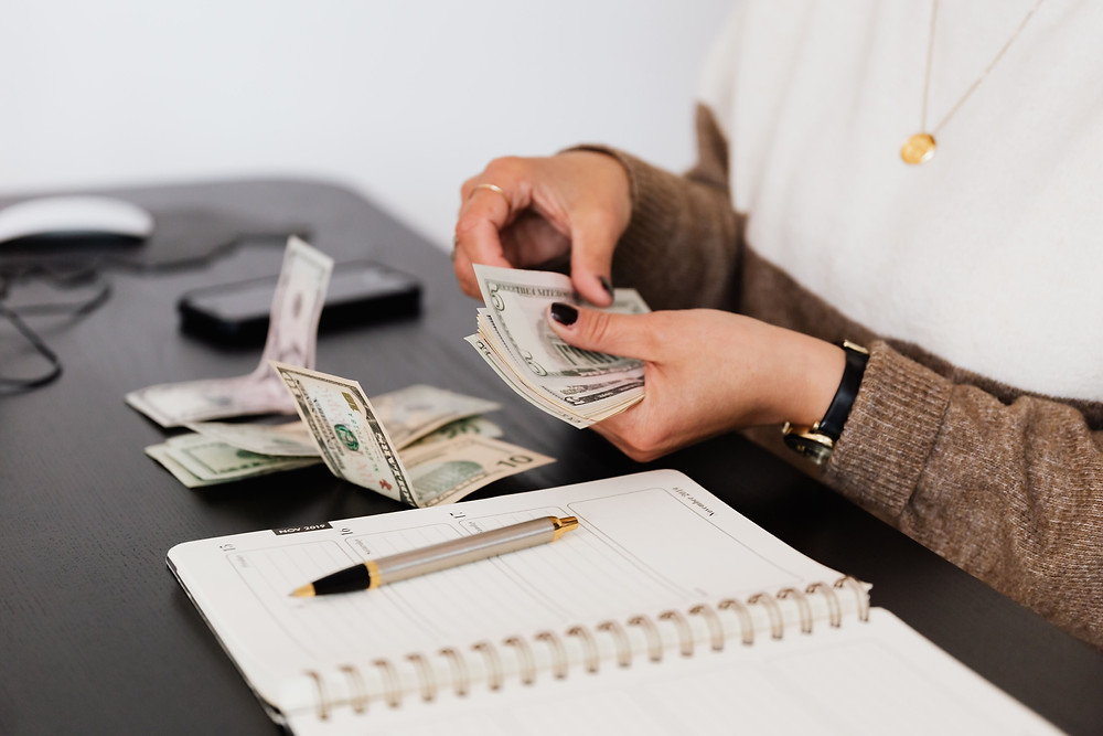 Woman counting money and making a budget