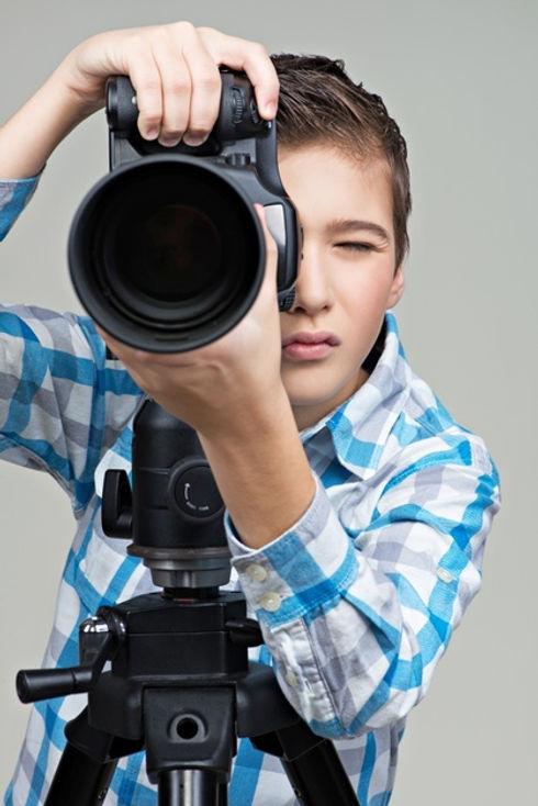 menino-com-camera-tirando-fotos-menino-com-camera-dslr-no-tripe_186202-6737.jpg