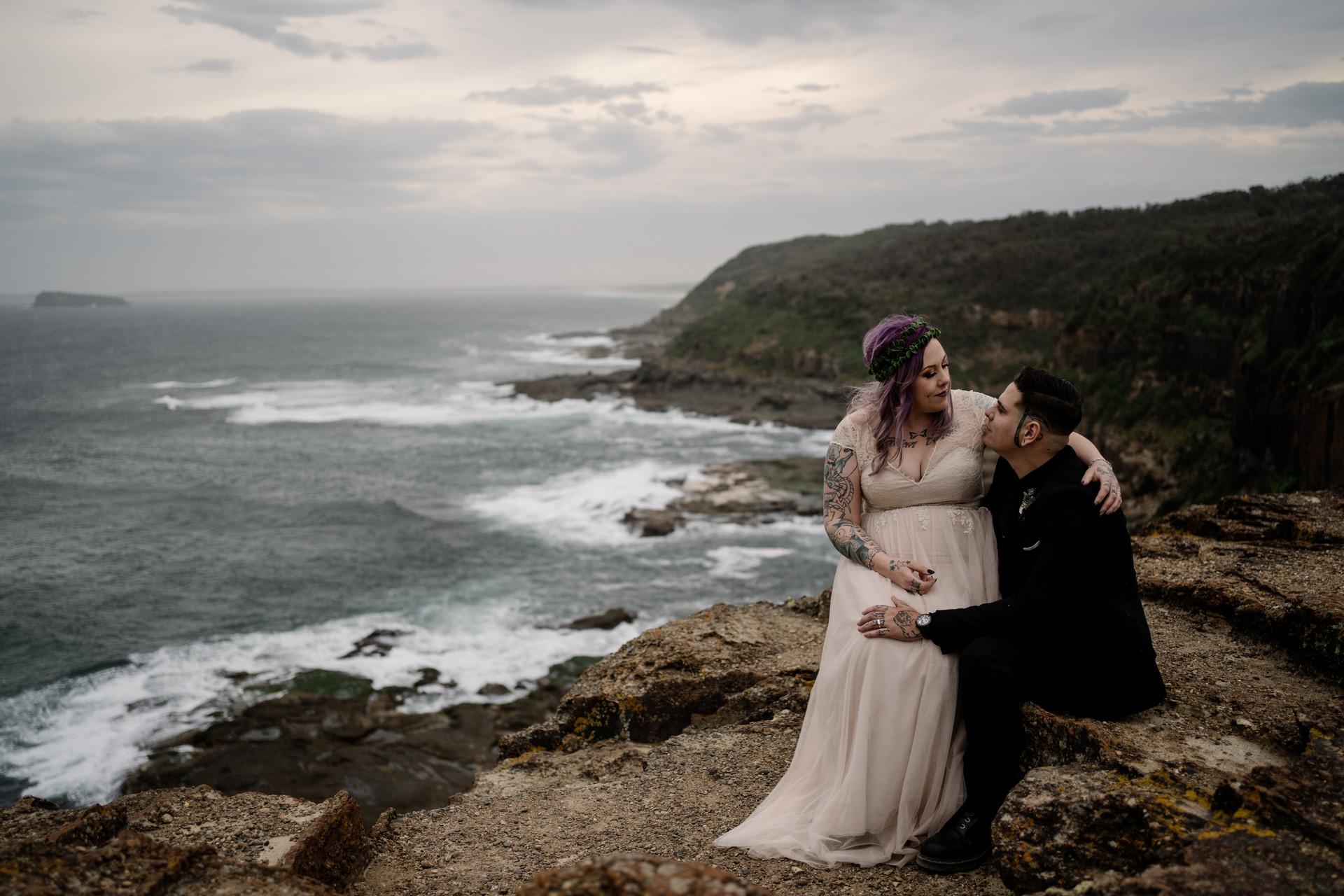 Bride sitting on groom's lap at beach