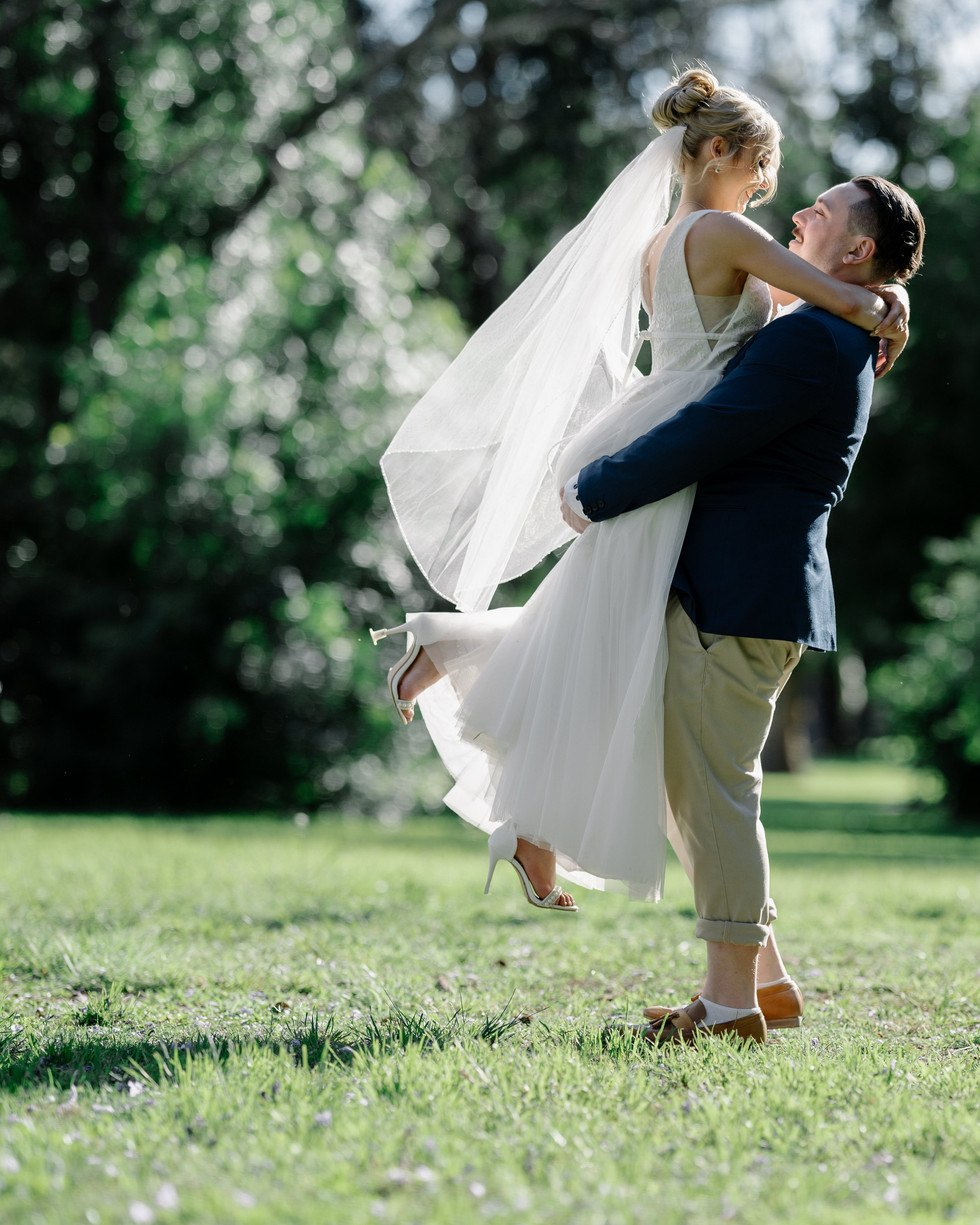 Bride and groom posing for camera with woman in air