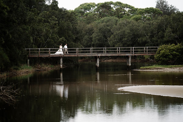 Bride and groom holding hands walking across bridge over water with reflection and bush backdrop after wedding ceremony