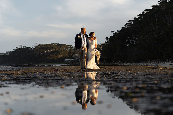 Bride and groom walking on coastal plateau with sunset light glowing highlights