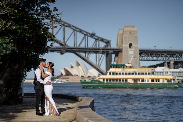 Bride pulling groom in for a passionate kiss with sydney ferry, sydney harbour bride and sydney opera house in backdrop