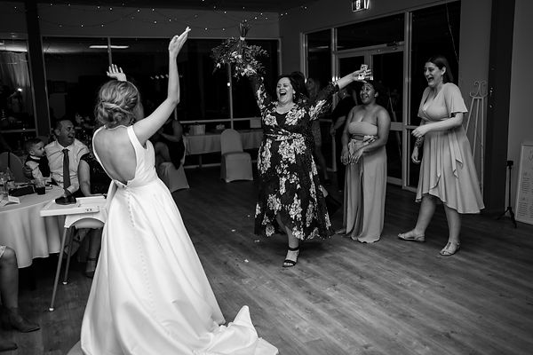 Bride tossing flower boquet at wedding reception and guests cheering