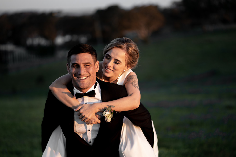 Couple posing for camera / Bride on Groom's Back