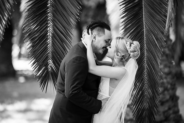 Bride pulling groom in for a passionate kiss after wedding ceremony