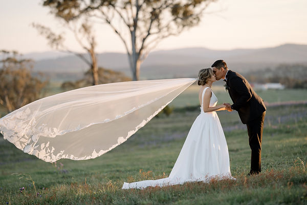 Stunning wedding photo of bride and groom kissing with wedding veil blowing softly in the wind, sunset glow warming the highlights