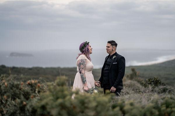 Destination wedding photo of bride and groom with coastal backdrop
