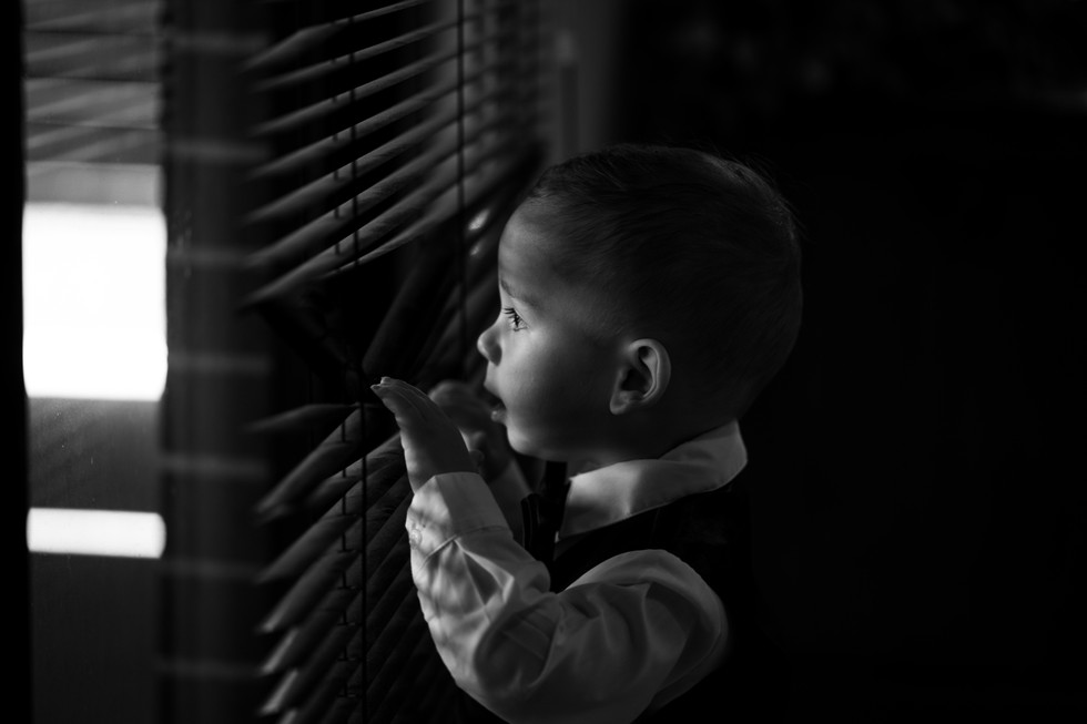 Black and white image of child looking through shades