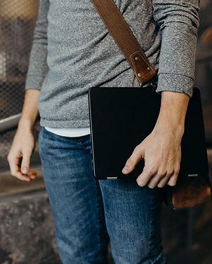 Mann, der Laptop hält