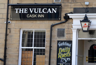 The Vulcan: Vinyl lettering on a tray sign lit by trough lighting.