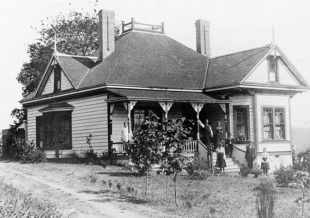 Family standing on front steps and porch of house.