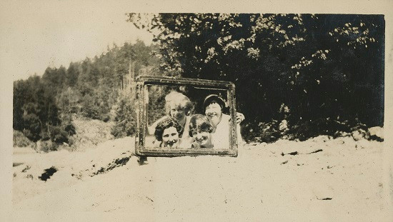 Four women peeking through an empty frame