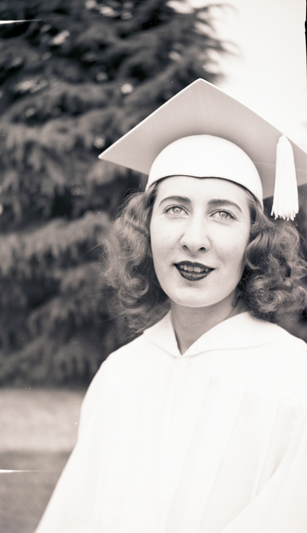 Woman wearing graduation cap and gown.