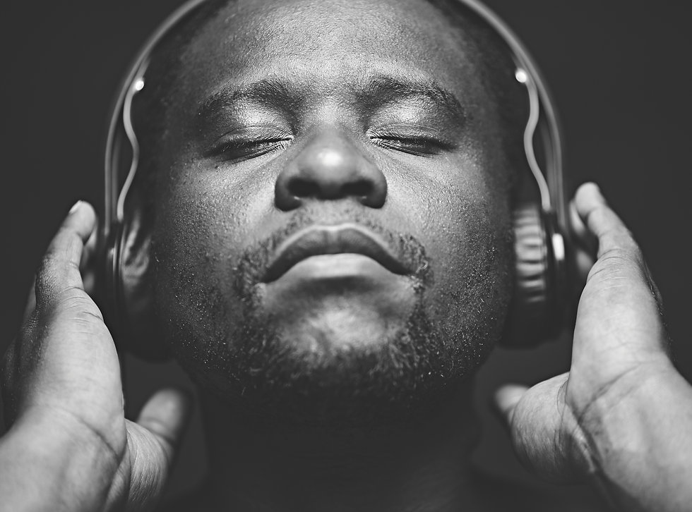 African-American guy with headphones listening to his favourite music.jpg