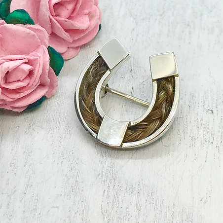 Horseshoe brooch in Sterling silver with a braid of horse hair