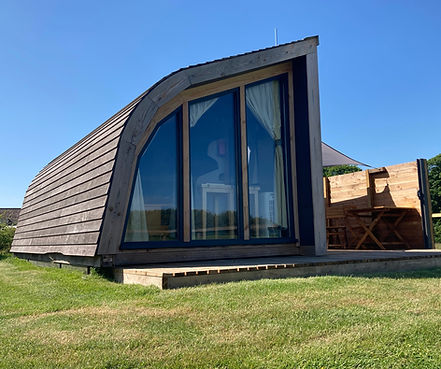 Large end windows of curved wooden pod in scenic countryside setting