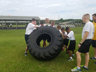 Young Marines flipping a tractor tire for team building