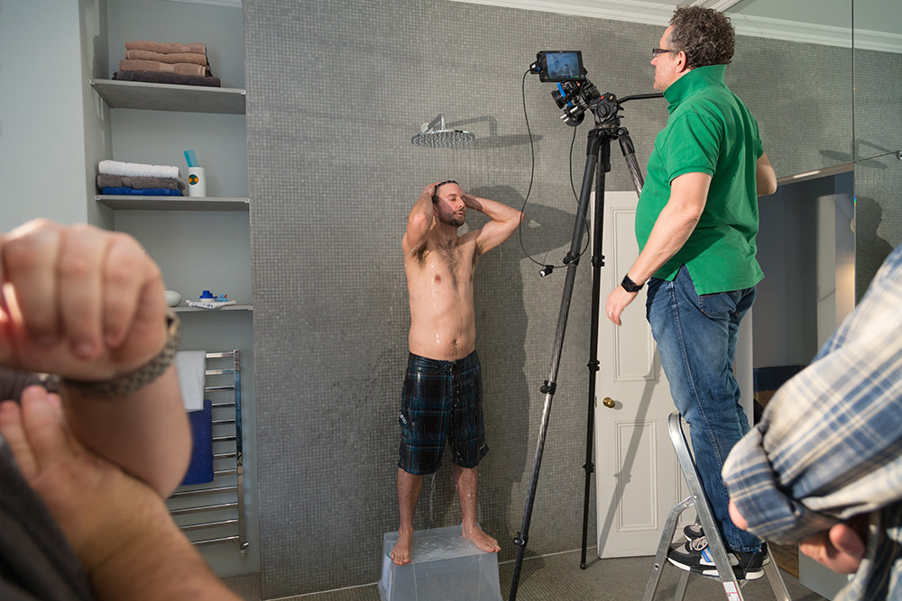 Behind the scenes image of film maker Jeremy Baile at RGB Digital shooting a man in the shower at a London location house