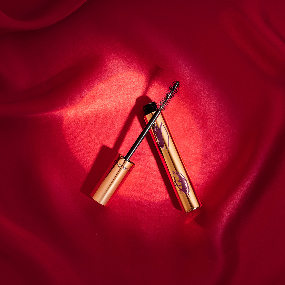 creative product photography of mascara on a red fabric background lit with a spotlight