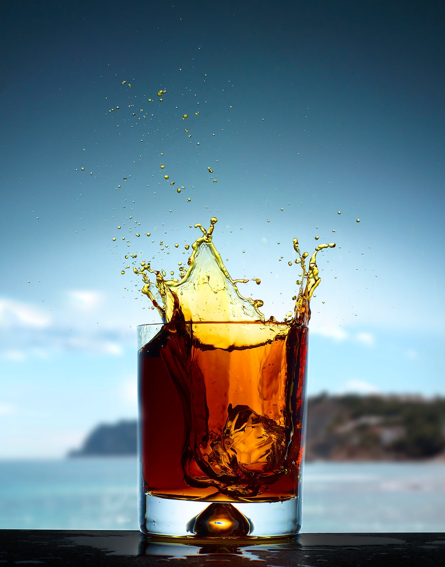 Drink photography of an ice cube splashing into a rocks glass with a sea view behind