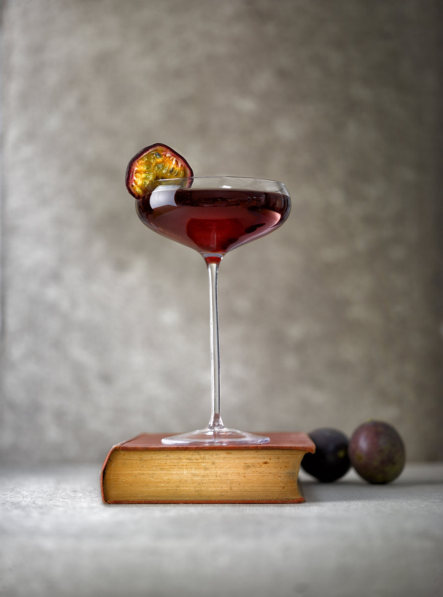 Drink photography of a passion fruit cocktail in an elegant glass on a book