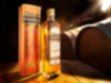 Drink photography of Bushmills Irish Whiskey in a distilliary with barrels and sunlight.