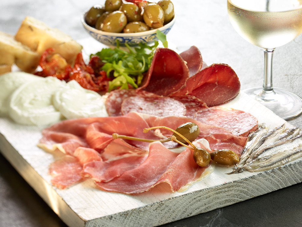 food photography of a served meat, cheese, bread and olive platter with white wine, in a restaurant kitchen setting. Shot on location by RGB Digital Ltd, London photography studio