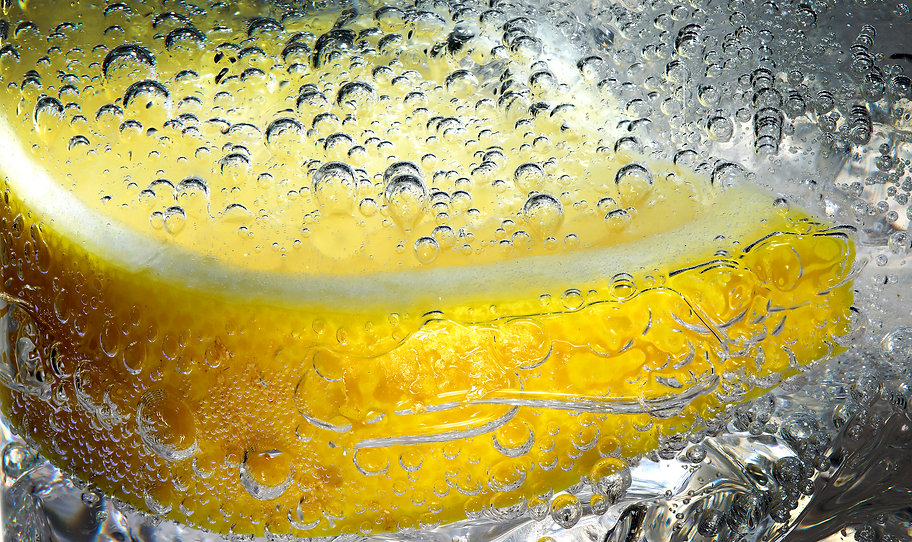 Drink photography of a close up of a lemon slice with bubbles