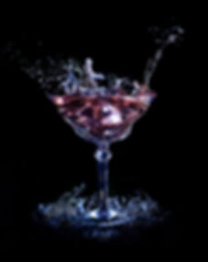 Drink photography of a martini glass with liquid splashing in and around the glass
