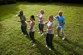 Foto de pessoas fazendo Yoga ao ar livre, com roupas confortáveis