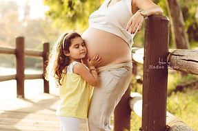 ילדה מחבקת בטן של אמא