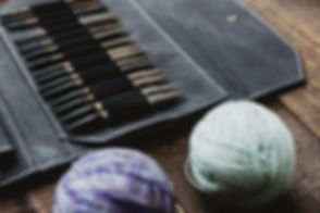 knitting-needles-and-yarn-on-a-wooden-ta