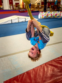 Child happily swinging from rope upside down