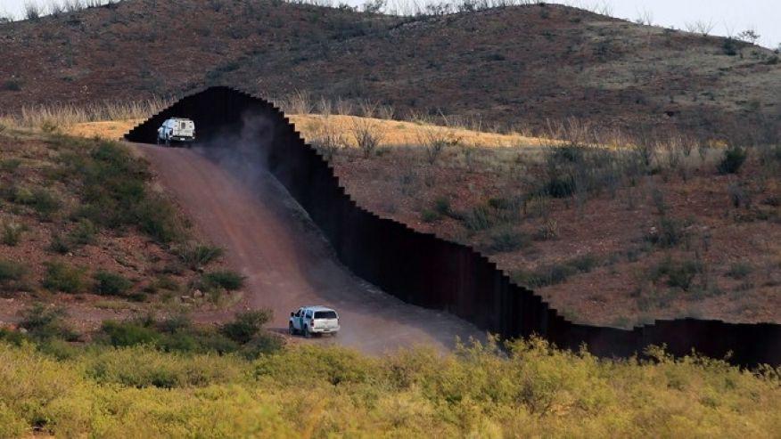 Vehicles patrol border fence.  Photo credit AP.