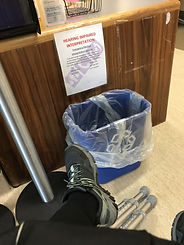 Photograph of a person's black pant leg and black shoe; from under shoe you see the bottom portion of two silver crutches with rubber tips. The person is not visible but is facing a small wooden desk, with a sign made of letter size pattern hanging from the top of the desk. The sign states in red letters at top of page , Hearing impaired interpretation. Mid page is black writing that is covered by large grey symbols, one is a handset, one is a person with two smaller people beside them, the third is not legible. A blue recycle bin with clear plastic bag inside sits in front of desk.