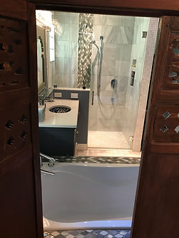 Photo through an asian window, into master bathroom. Tub with faucet in foreground, vanity to the left and zero threshold shower in background, with telescoping handheld shower head.