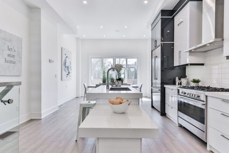 Kitchen with some white cabinets and black cabinets, the kitchen island has two different heights creating two different work surfaces. The sink with tall faucet is on the island. D Shaped handles contrast with the cabinets,  very large windows in dining area at far end of the room, pot lighting, contrasted white walls with low glare grey flooring.
