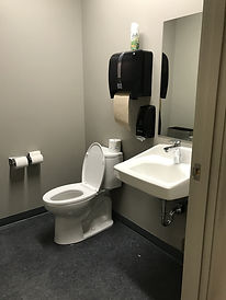 Photograph of a washroom for staff in a bank. Regular toilet with open lid. No grab bars. Two toilet roll dispensers to the left of toilet at the front of the toilet on the wall( when facing toilet). On the wall behind the toilet there is a two handed paper towel dispenser, approximately 2 feet from top of toilet. On the dispenser sits a can of air freshner, that could fall beside toilet. Wall sink with mirror from top of sink to approximately 7 feet.