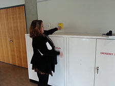 Donna is standing beside a shoulder height white emergency storage cabinet, reaching at shoulder height, elbow straightened across the top of cabinet to yellow emergency call button; demonstrating how someone using a wheelchair would not be able to reach the emergency button