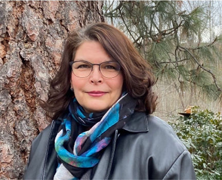 Photo of Donna smiling, medium length brown hair, glasses, black leather jacket and blue scarf, standing in front of huge ponderosa pine.