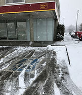 A snow covered bank handicapped parking spot, the concrete painted disabled parking sign is obstructed by snow. On the right side of the parking spot is snow covered a sidewalk ramped from parking area to the bank's front sidewalk.  The ramp has no handrails or raised edges and is completely covered in snow, snow is seen falling from sky. There is no handicapped parking sign at the sidewalk edge of the spot.