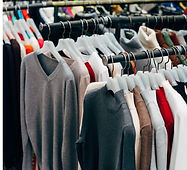 A store with mens sweaters hanging from hangers in rows that where the aisle is too narrow to pass through we easy, for anyone.