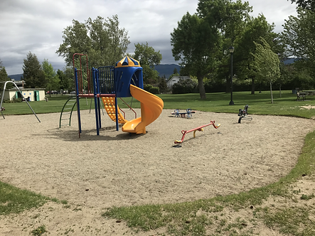 Photo of a playground, with a sand base, that is surrounded by patchy green grass. The playground has 3 small red teeter totters and one raised blue colored platform with two yellow slides and 1 blue ladder, extending from the platform to the ground. One slide is straight, the second slide spirals down to approximately 1 foot from the sand. On the left side in the background there is a swing set and a public washroom. The sky is cloudy, the park has large trees. There are no children or adults in the photo.