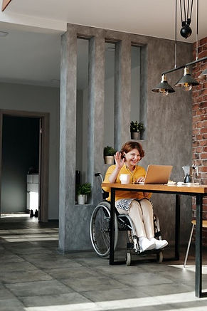Lady in orange shirt seated at table in front of laptop, white coffee mug to her right, she is seated in wheelchair, in room with large sized grey tile flooring, Red brick on one wall, grey wall with three cutouts behind her and sun streaming in.