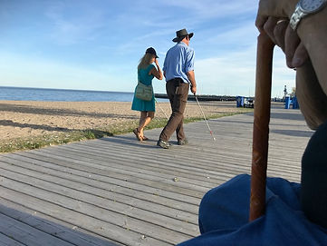 A femal and a male with an australian hat, are walking away along a board walk. In the background is a large lake and sandy shoreline. In the foreground is the wooden cane, watch and hand of a senior who is seated on the boardwalk.