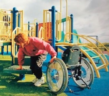 A small child is transfering from their wheelchair onto a transfer station on a playground. The surfacing is rubber and blue. The playground structure is yellow, blue, green and red.