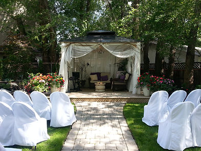 Photograph of an outdoor wedding venue, with an interlocking brick pathway that leads to a small wooden 1 step platform stage. A covered stage is adorned with white curtains. Two rows of chairs sit on both sides of the pathway on grass facing the stage. These chairs are covered in white fabric chair covers that drape to the ground. Flower arrangements are to the left of the platform stage facing the chairs. Shade from tall trees dapples the ground.