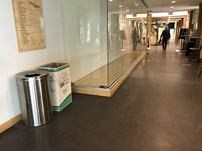 Photograph looking down a building hallway, on left close up is recycle bin and waist height silver round garbage bin against the wall. Just past the recycle bin, there is a glassed floor to ceiling display case. The glass does not have markings to indicate the presence of glass. The glass case has reflections by no hazard or caution signs, which is a hazard. Down the hallway is person walking away, their impression is on the glass. The lighting is low.